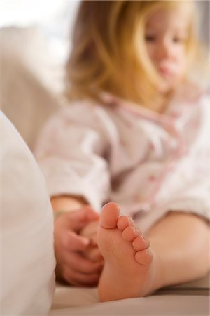 Close-up of a baby girl sitting on the bed Stock Photo - Rights-Managed, Code: 837-02381185