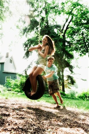 preteen girl boyfriends - Teenage girl swinging on a tire swing with a young man pushing her Stock Photo - Rights-Managed, Code: 837-02381350