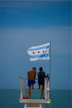 Tourists standing on a lifeguard hut, Oak Street Beach, 1000 North Lake Shore Drive, Chicago, Illinois, USA Stock Photo - Rights-Managed, Code: 837-02382104