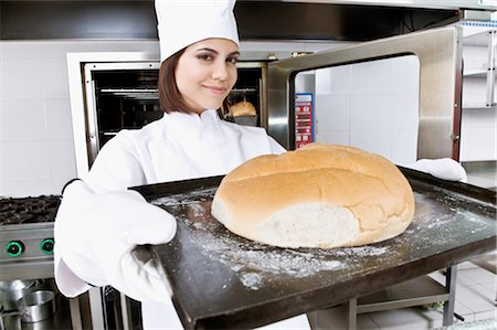 Female chef holding a bun in a tray Stock Photo - Rights-Managed, Code: 837-03069682