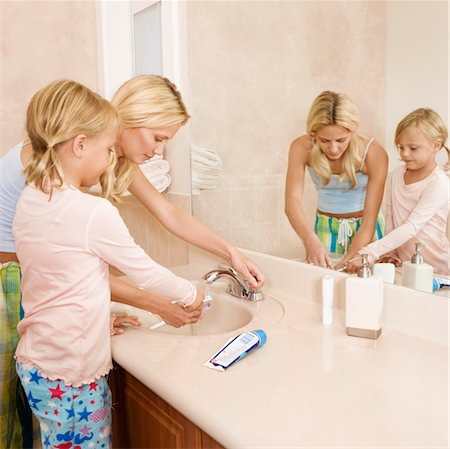 Woman helping her daughter in brushing teeth Stock Photo - Rights-Managed, Code: 837-03074270