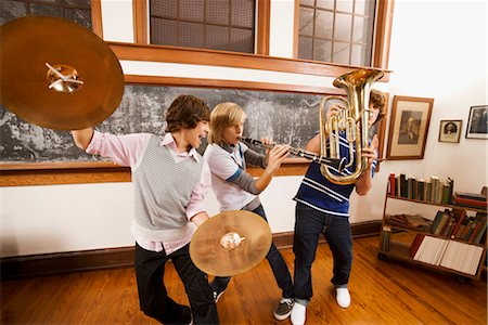 Three students playing musical instruments in a classroom Stock Photo - Rights-Managed, Code: 837-03074639