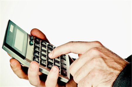 finger holding a key - Close-up of a man's hand using a calculator Stock Photo - Rights-Managed, Code: 837-03070348