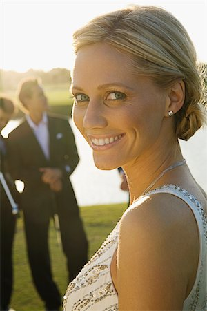Portrait of a bride smiling with two golfers in the background,Biltmore Golf Course,Coral Gables,Florida,USA Stock Photo - Rights-Managed, Code: 837-03070534
