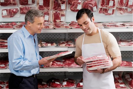 Sales clerk giving meat to a man in a supermarket Stock Photo - Rights-Managed, Code: 837-03070561