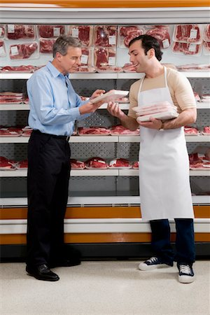 Sales clerk assisting a customer choosing meat in a supermarket Stock Photo - Rights-Managed, Code: 837-03071184