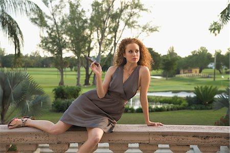 Woman sitting on balustrade and smoking a cigar,Biltmore Hotel,Coral Gables,Florida,USA Stock Photo - Rights-Managed, Code: 837-03071572