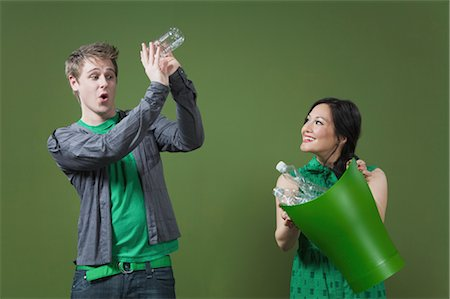 Woman holding a recycling bin and a man looking into an empty water bottle Stock Photo - Rights-Managed, Code: 837-03071782