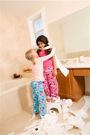 Two girls playing with toilet paper rolls in the bathroom Stock Photo - Rights-Managed, Code: 837-03071847