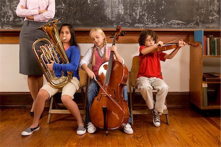 Three students playing musical instruments in a classroom Stock Photo - Rights-Managed, Code: 837-03072900