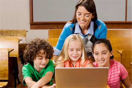 Students with their teacher using a laptop in a classroom Stock Photo - Rights-Managed, Code: 837-03073038