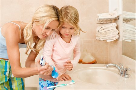 Woman helping her daughter in brushing teeth Stock Photo - Rights-Managed, Code: 837-03073745