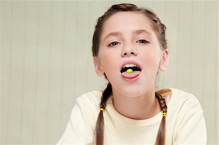 preteen open mouth - Girl with a candy on her tongue Stock Photo - Rights-Managed, Code: 837-03184996