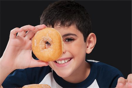 preteens fingering - Boy holding a donut in front of his eye Stock Photo - Rights-Managed, Code: 837-03183322