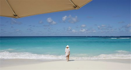 Woman standing on a tropical beach with umbrella in foreground Stock Photo - Rights-Managed, Code: 832-03724416
