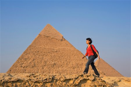 Woman with rucksack walking along ancient wall in front of Pyramids Stock Photo - Rights-Managed, Code: 832-03724663