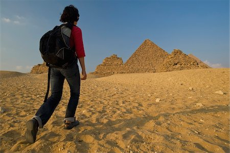Woman with rucksack walking towards Pyramids at dusk Stock Photo - Rights-Managed, Code: 832-03724769