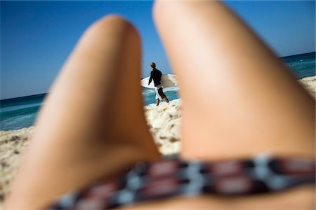 Surfer viewed through womans legs lying on Bondi Beach Stock Photo - Rights-Managed, Code: 832-03723715