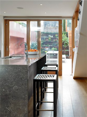 Bar stools at breakfast bar with full-height glass doors to garden, UK. Architects: STUDIO BEDNARSKI LTD Stock Photo - Rights-Managed, Code: 845-05837805