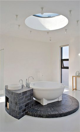 Bathroom, with a circular skylight that allows light to flood down onto the circular bath and its brick plinth. House of an art collector on the northern outskirts of Beijing. Designed by neighbouring artist Shao Fan, who also designed the furniture, this is part of a compound of several friends. Stock Photo - Rights-Managed, Code: 845-05838380