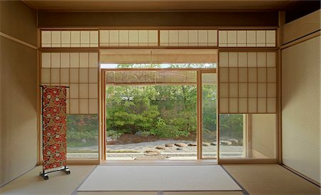 Traditionally Japanese sparsely furnished room with view through sliding doors to garden Stock Photo - Rights-Managed, Code: 845-05838903