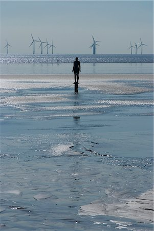 One of the 100 iron men at Crosby Beach as part of Anthony Gormley's Another Place, with wind generators behind, Liverpool, Merseyside, England Stock Photo - Rights-Managed, Code: 845-03552607