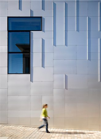 Female figure walking past the cladded facade of Cornerstone Arts Centre, Didcot. Architects: Ellis Williams Architects Stock Photo - Rights-Managed, Code: 845-03777447
