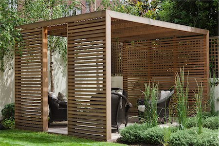 Slatted cedar pavilion on the right side of the lawn on the upper level of the garden. Silver birches along the boundary wall. Hebe and grasses on the right. Architects: Modular Stock Photo - Rights-Managed, Code: 845-03777659