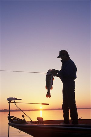 1990s SUNSET SILHOUETTE FISHERMAN HOLDING LARGEMOUTH BASS Stock Photo - Rights-Managed, Code: 846-05645778