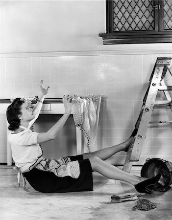 1940s WOMAN HOUSEWIFE FALLING FROM STEP LADDER IN KITCHEN WHILE WASHING WINDOW Stock Photo - Rights-Managed, Code: 846-05645845