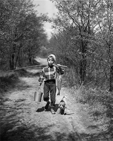 1950s BOY BEAGLE PUPPY WALKING DOWN COUNTRY ROAD WHISTLING CARRYING FISHING POLE PAIL FISH Stock Photo - Rights-Managed, Code: 846-05645865