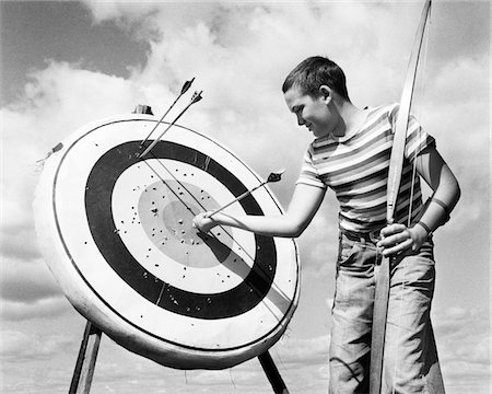 1960s BOY JEANS STRIPED T-SHIRT HOLDING BOW & PULLING ARROW OUT OF TARGET BULL'S-EYE Stock Photo - Rights-Managed, Code: 846-05645870
