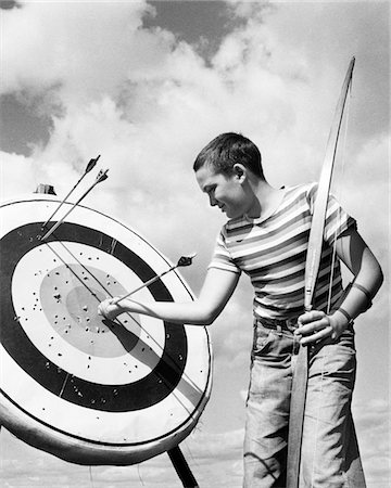 1950s BOY JEANS STRIPED T-SHIRT HOLDING BOW & PULLING ARROW OUT OF TARGET BULL'S-EYE Stock Photo - Rights-Managed, Code: 846-05645894