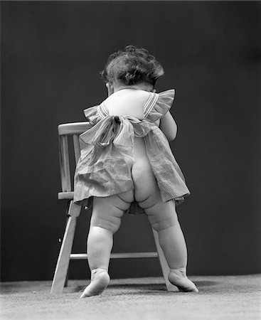 1940s BACK END VIEW OF NUDE GIRL BABY WEARING PINAFORE APRON Stock Photo - Rights-Managed, Code: 846-05645955
