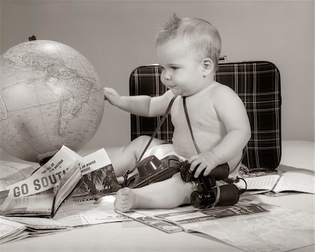 1960s BABY SEATED LOOKING AT GLOBE WITH CAMERA BINOCULARS SUITCASE & TRAVEL BROCHURES Stock Photo - Rights-Managed, Code: 846-05645964