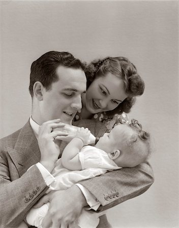 1940s FATHER CRADLING BABY DAUGHTER FEEDING HER BOTTLE WITH MOTHER LOOKING OVER HIS SHOULDER Stock Photo - Rights-Managed, Code: 846-05645979