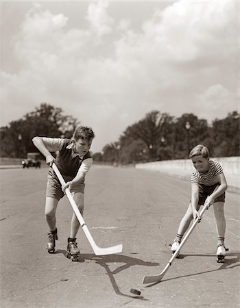 roller skate - 1930s - 1940s 2 BOYS WITH STICKS AND PUCK WEARING ROLLER SKATES PLAYING STREET HOCKEY Stock Photo - Rights-Managed, Code: 846-05645990
