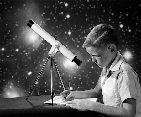 1960s BOY SITTING AT TABLE WITH TELESCOPE & STARS IN BACKGROUND WRITING IN NOTEBOOK Stock Photo - Rights-Managed, Code: 846-05646056
