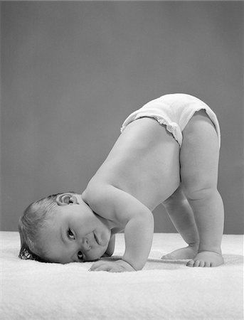 1950s SIDE VIEW OF PORTRAIT BABY IN DIAPER WITH CHEEK TO FLOOR AND BOTTOM IN AIR Stock Photo - Rights-Managed, Code: 846-05646114