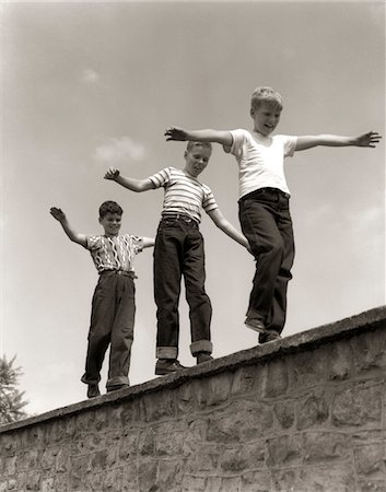 1950s THREE LAUGHING BOYS WALKING ON TOP OF STONE WALL ARMS OUT BALANCING PLAYING FOLLOW THE LEADER Stock Photo - Rights-Managed, Code: 846-05646111