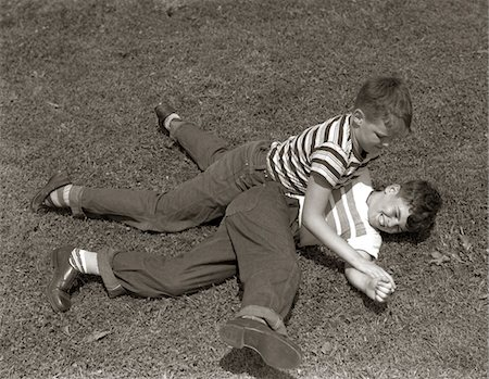 1950s TWO BOYS WEAR TEE SHIRTS BLUE JEANS PLAYING ROUGH FIGHTING WRESTLING ON THE GRASS Stock Photo - Rights-Managed, Code: 846-05646112