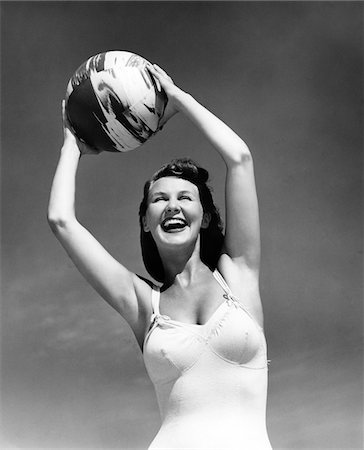 1940s SMILING WOMAN IN WHITE BATHING SUIT HOLDING A BEACH BALL OVER HER HEAD OUTDOOR Stock Photo - Rights-Managed, Code: 846-05646142