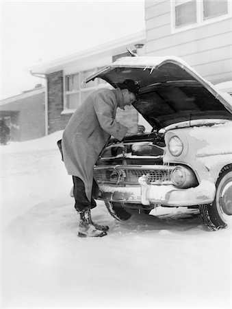 1950s MAN WINTER DRIVEWAY TRYING TO START FIX CAR HOOD UP Stock Photo - Rights-Managed, Code: 846-05646158