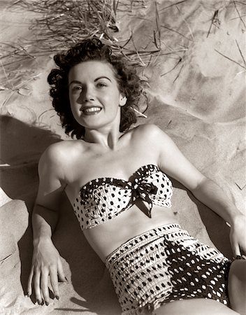 1950s SMILING BRUNETTE WOMAN WEAR POLKA DOT TWO PIECE BATHING SUIT LAYING ON SAND Stock Photo - Rights-Managed, Code: 846-05646151