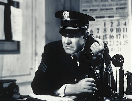 1930s - 1940s CONCERNED DETERMINED MAN POLICE SERGEANT IN STATION HOUSE TALKING ON CANDLE STICK TELEPHONE Stock Photo - Rights-Managed, Code: 846-05646168