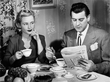 1940s COUPLE BREAKFAST TABLE IMPATIENT WOMAN LOOKING AT MAN READING NEWSPAPER Stock Photo - Rights-Managed, Code: 846-05646160