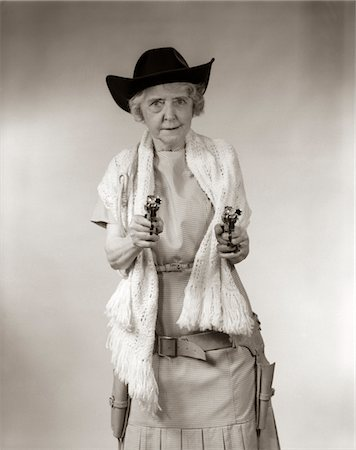 1950s GRANNY COWGIRL WEARING HAT & SHAWL & POINTING 2 PISTOLS AND LOOKING AT CAMERA Stock Photo - Rights-Managed, Code: 846-05646207