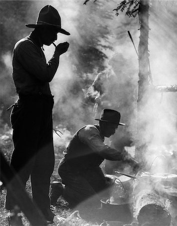 1920s THREE MEN COWBOYS CAMPING ONE MAN SMOKING PIPE ONE MAN COOKING OVER CAMPFIRE MOODY SILHOUETTE Stock Photo - Rights-Managed, Code: 846-05646228
