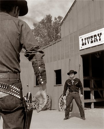 1950s - 1960s TV COWBOYS IN FRONT OF LIVERY STABLE READY TO DRAW PISTOLS IN GUNFIGHT Stock Photo - Rights-Managed, Code: 846-05646221