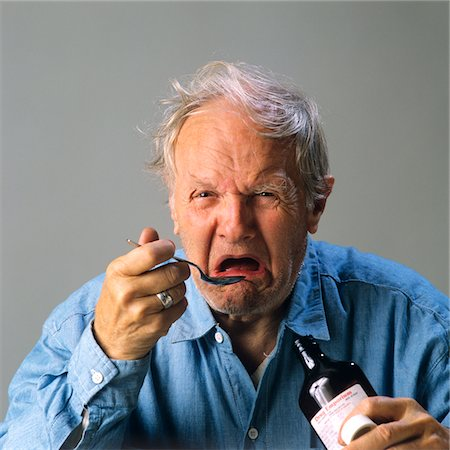 1970s SENIOR MAN TAKING SPOONFUL OF MEDICINE WITH BAD TASTE Stock Photo - Rights-Managed, Code: 846-05646240